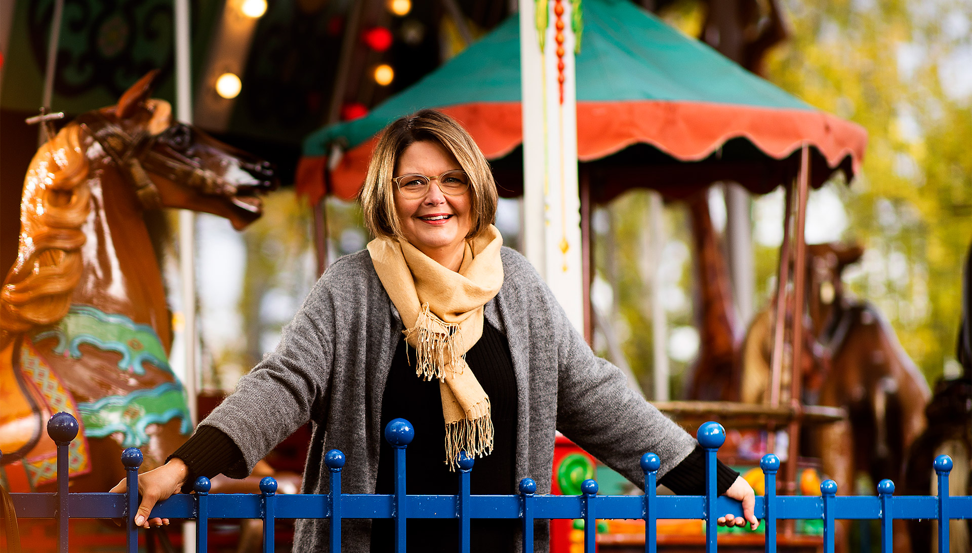 MLL:n pääsihteeri Milla Kalliomaa hymyilee karusellin edessä Linnanmäellä.