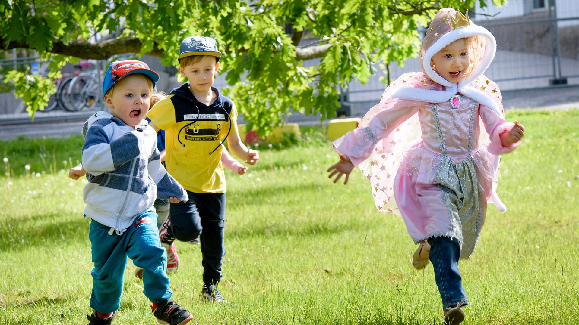 Prinsessapukuinen tyttö ja kaksi pientä poikaa juoksevat ulkona nurmikolla.