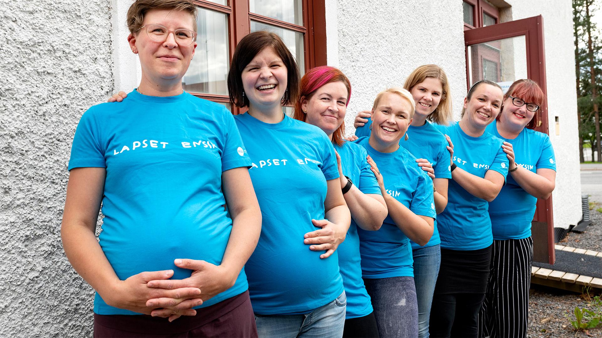 Seitsemän hymyilevää vapaaehtoista, jotka seisovat talon edustalla. Heillä on päällään turkoosit Lapset ensin -T-paidat.