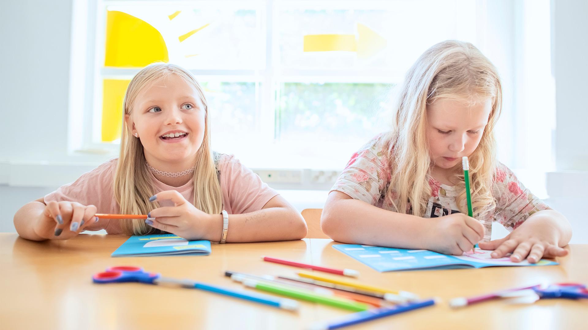 Kaksi alakoululaistyttöä piirtää pöydän ääressä ikkunan edessä värikynillä Aikaseikkailu-vihkoon.
