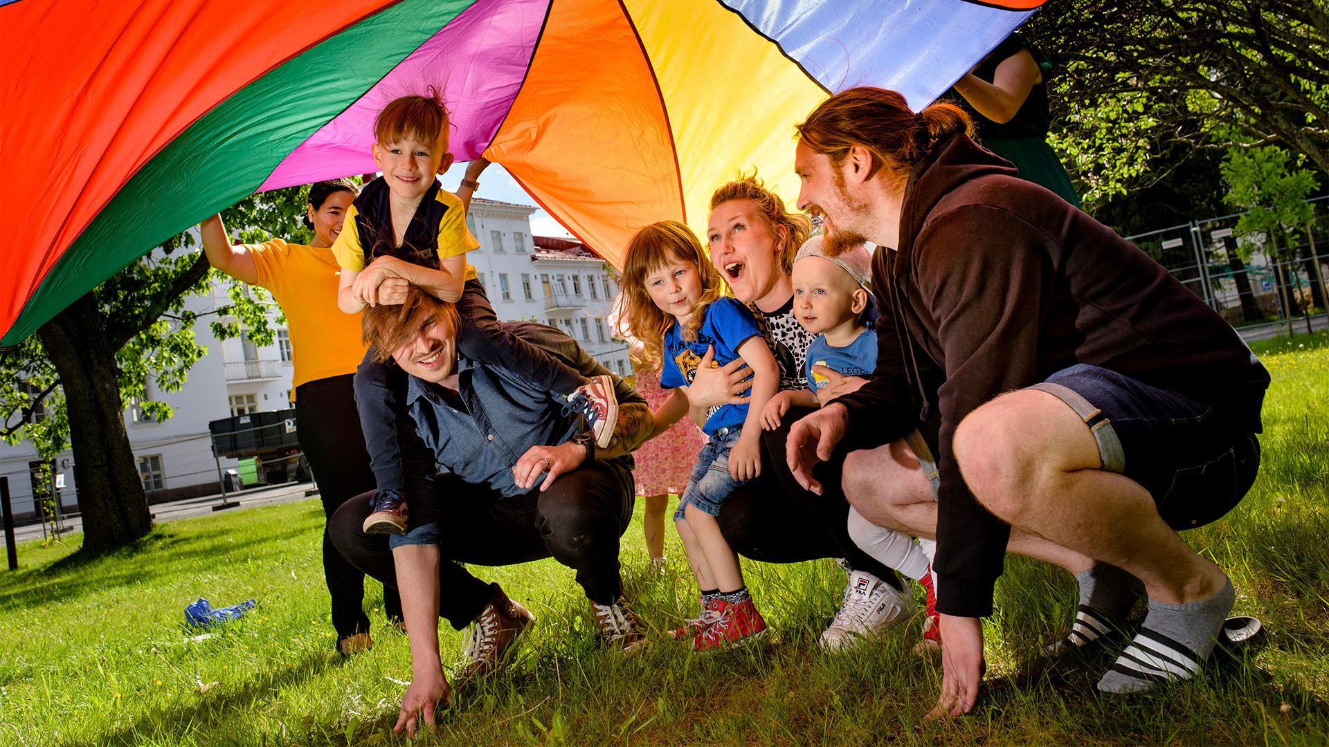 Nauravia lapsia, äitejä ja isiä kyykistelee nurmikolla sateenkaaren väreissä olevan leikkivarjon alla.