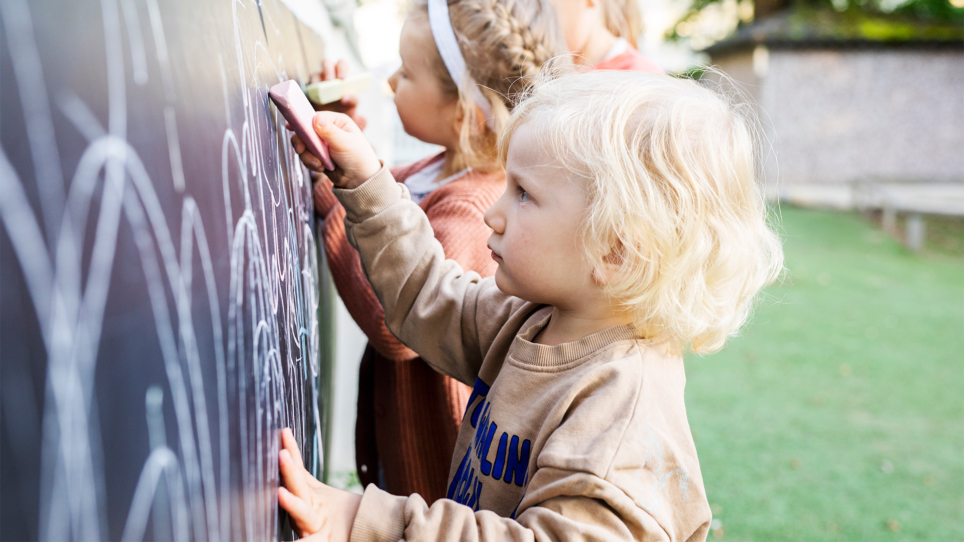 Alle kouluikäisiä lapsia piirtää ulkona liitutauluun.