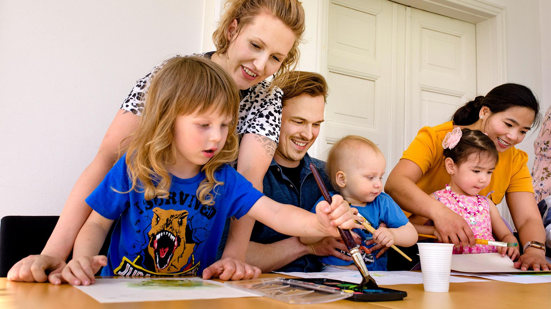 Hymyileviä aikuisia ja lapsia maalaa vesiväreillä pöydän ääressä MLL:n perhekahvilassa.