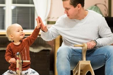 Isä ja lapsi istuvat keinuhevosilla